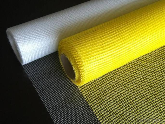 White alkali-resistant fiberglass mesh is unrolled on a paper cardboard box which is filled with rolls of packed fiberglass mesh.