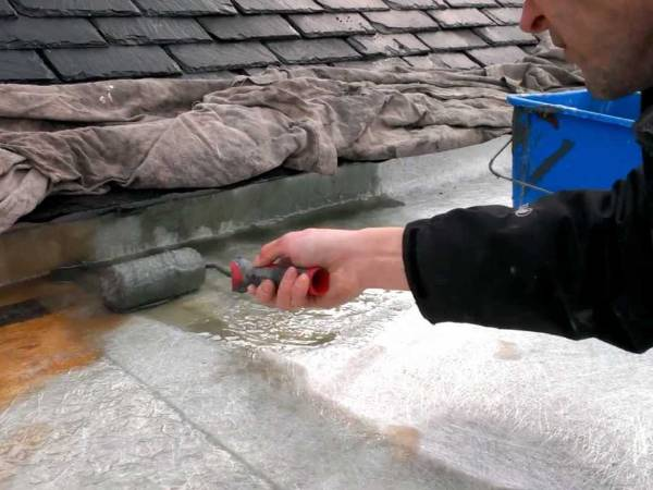 A man is rolling resin onto he fiberglass chopped strand mat.
